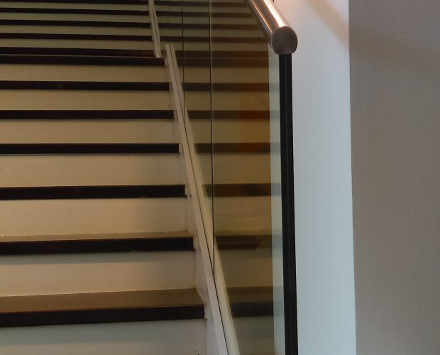 glass handrail down a stairs with handrail