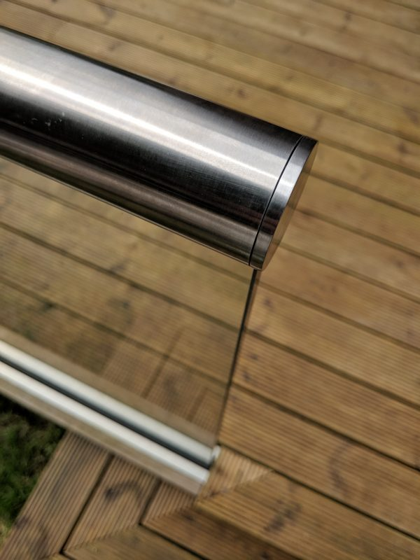 aluminox Slotted end cap on slotted handrail installed ontop a glass balustrade on decking